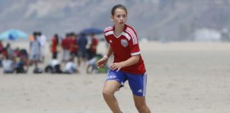 Girl Playing Soccer on Beach