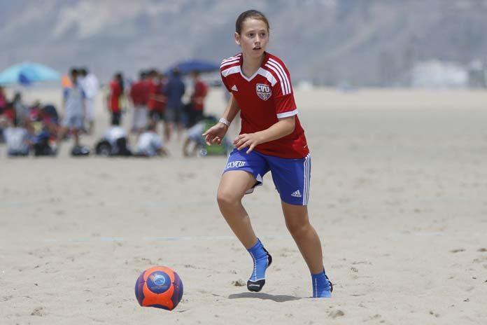 Girl Playing Soccer on Beach