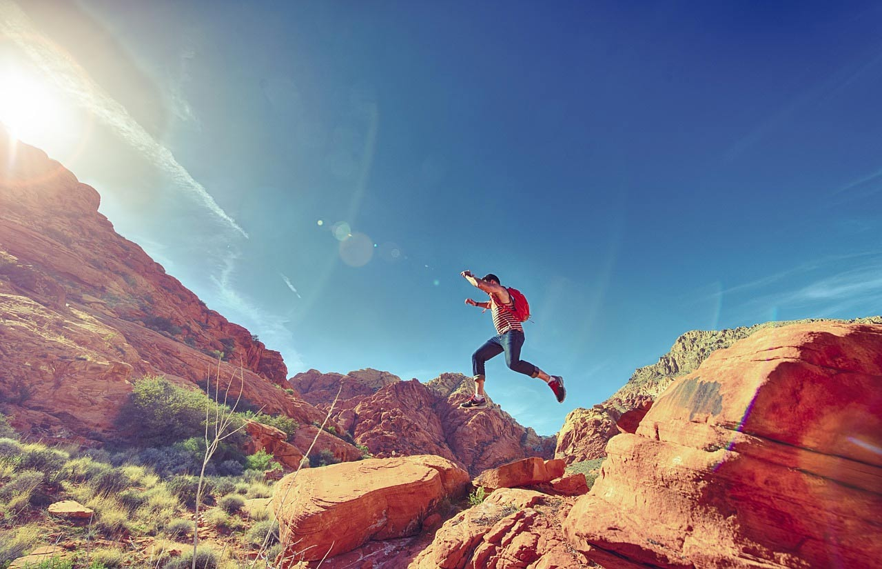 Hiker jumping off rocks