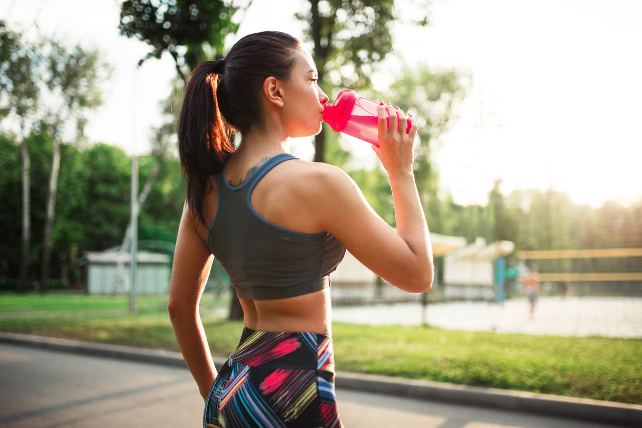 Girl Jogging and drinking health drink from sipper