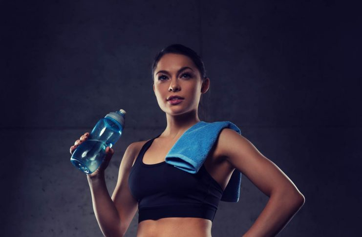 woman with towel drinking water from bottle in gym