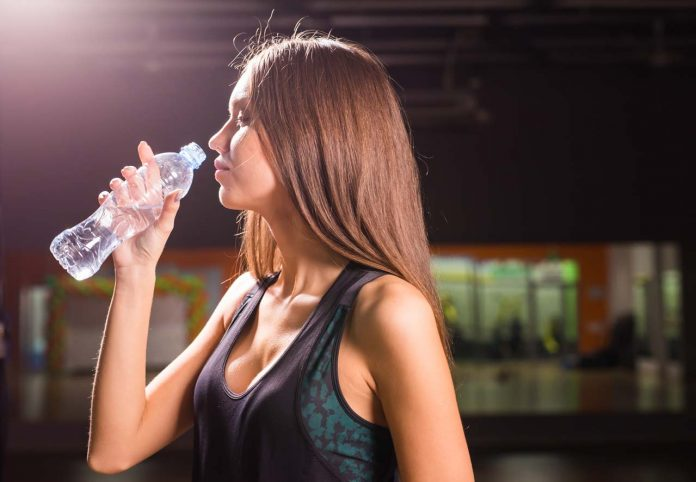 fitness woman drinking water from bottle