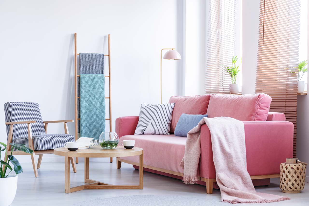 pink couch with cushions and blanket