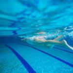 young girl swimming underwater in pool