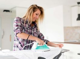 beautiful young woman is ironing clothes at home