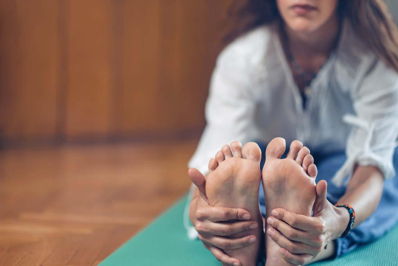 yoga woman in yoga studio seated forward bend