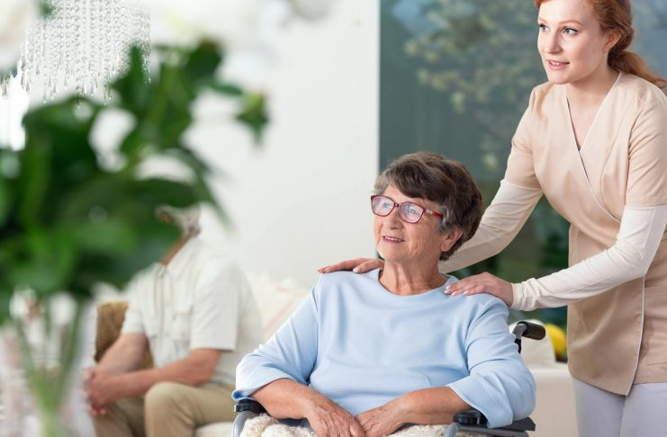 caregiver taking care of disabled elderly woman