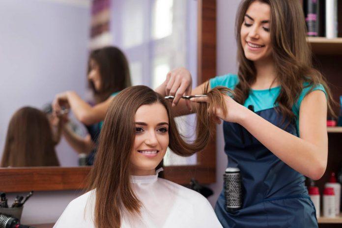 beautiful woman getting hair cut at salon