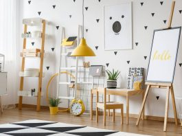 poster on easel and yellow lamp above carpet
