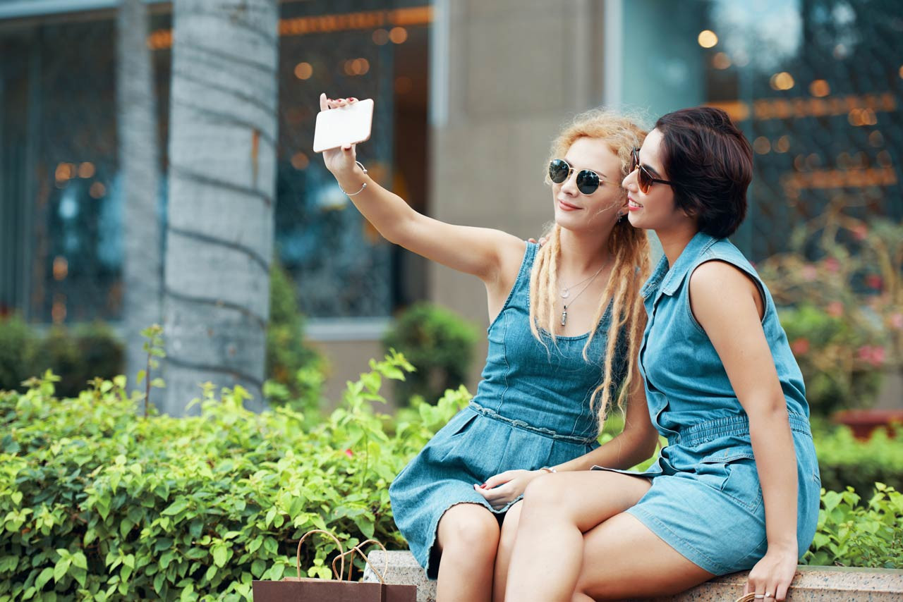 Girls taking selfie in denim dress