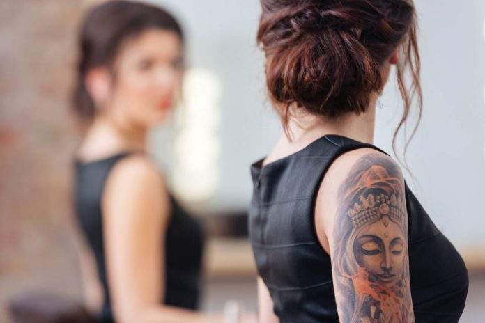 Woman with tattoo on hand standing in front of mirror