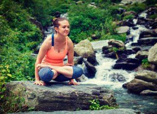 Woman doing Ashtanga Vinyasa Yoga arm balance asana Tolasana