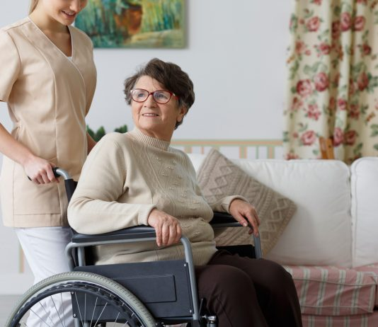 Old woman on wheelchair and her nursing assistance