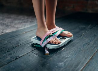 Womans feet on the scales tied with measuring tape