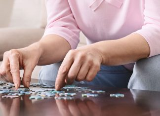 Elderly female hands trying to connect pieces of jigsaw puzzle