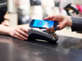 Woman's hand with mobile phone paying at checkout