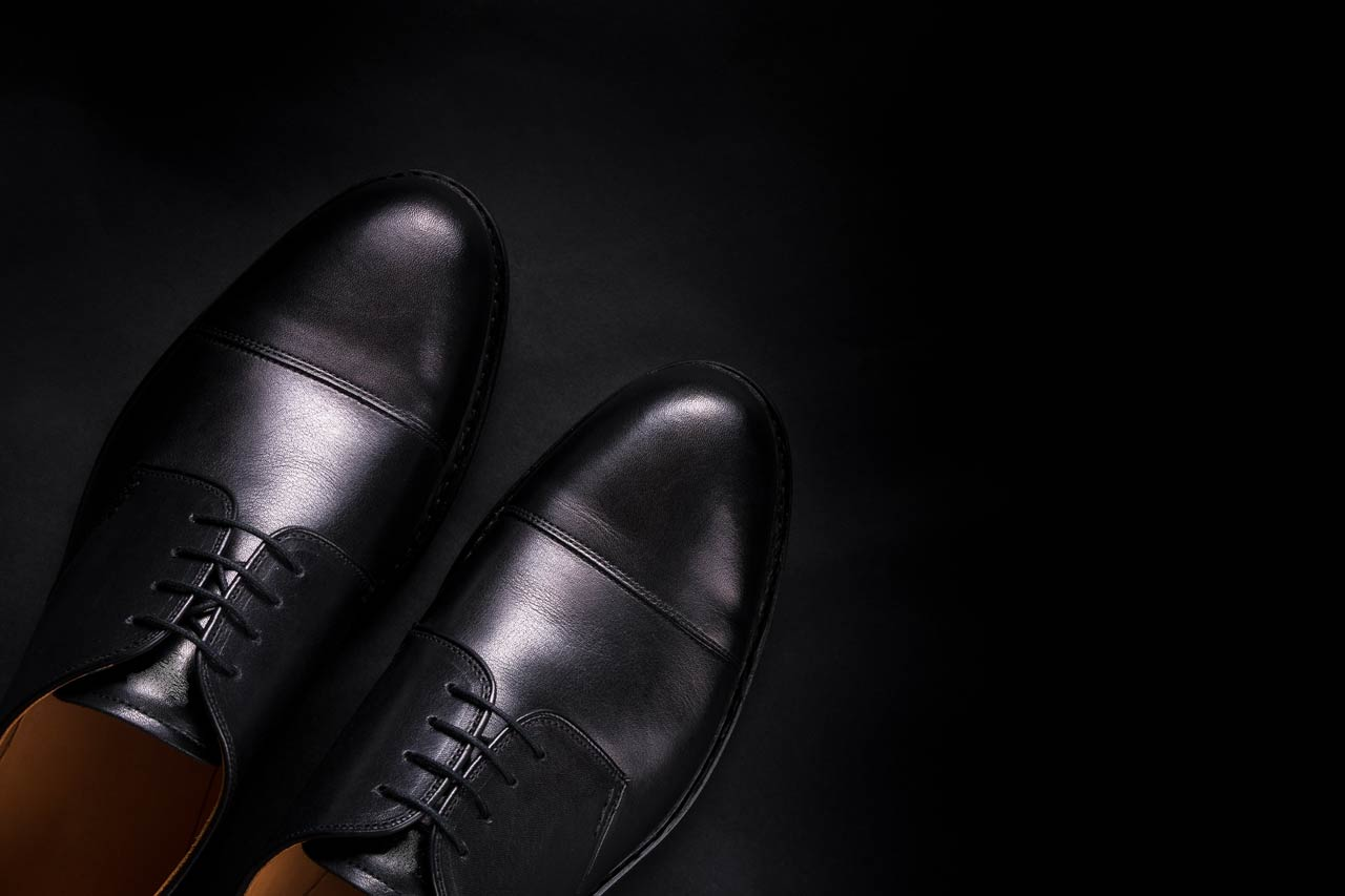 black oxford shoes on background top view