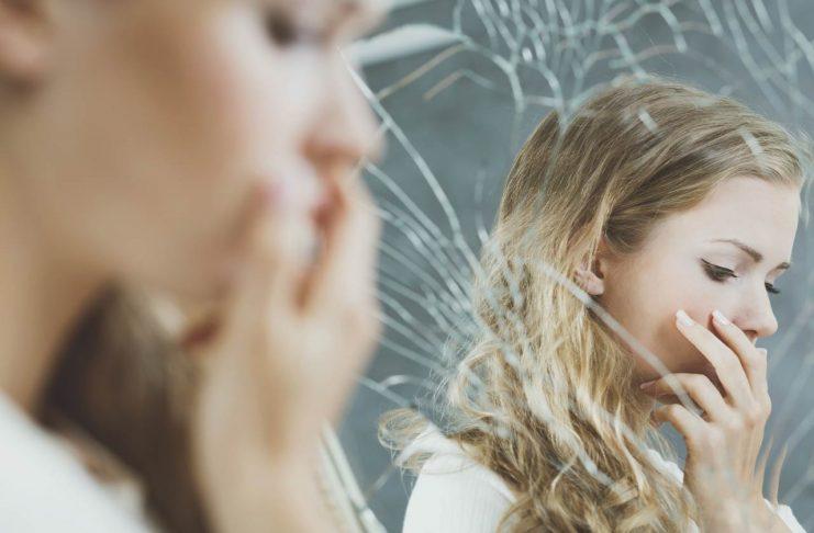 girl looking in broken mirror with low self esteem