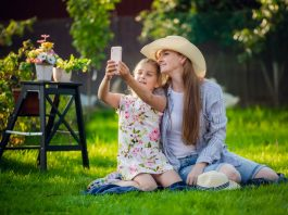 Smiling girl taking selfie with mother sitting on grass at backyard