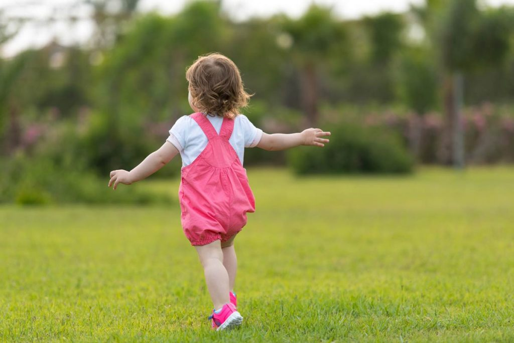 little girl playing in backyard