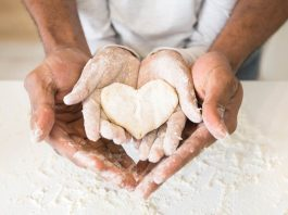 Afro man hands holding child hands with heart shaped pastry