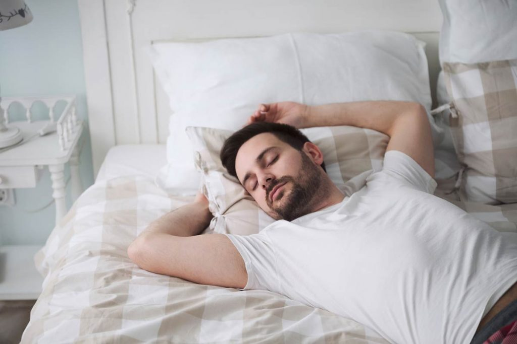 Handsome man sleeping on pillow in bed