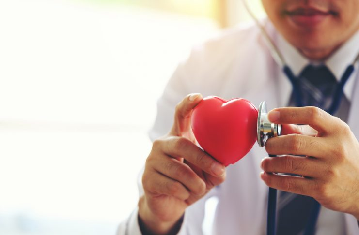 doctor holding hands with red heart in clinic office, Healthy lifestyle concept
