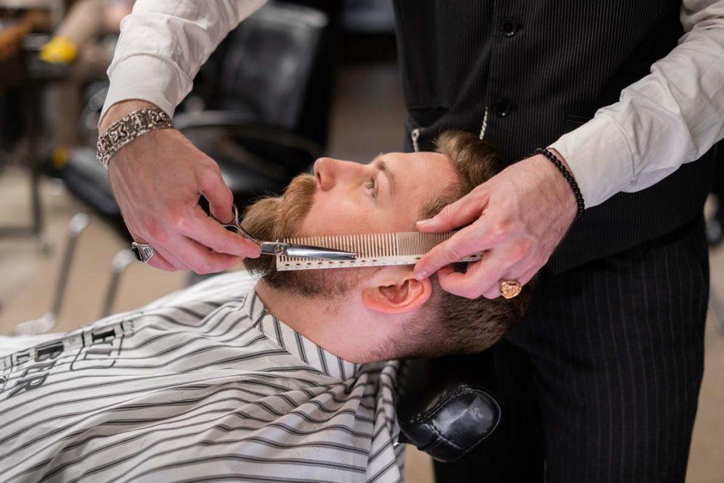 barber trimming beard